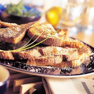 RECEPTJE - Wist je dat brood op de tweede plaats staat van meest verspilde voedingsmiddelen in Nederland? Dat doet ons bakkershart enorm veel pijn! Gelukkig zijn er heerlijke recepten waardoor je geen brood meer hoeft te verspillen! Vandaag het recept voor hartige wentelteefjes! INGREDIËNTEN (VOOR 4 PERSONEN): - 8 sneetjes oud wit- of bruinbrood - 1 citroen - 1 ei - 1/4 liter melk - 100 g geraspte oude kaas - 2 eetlepels verse Italiaanse kruiden, fijngehakt - 2 eetlepels bieslook, fijngehakt - versgemalen peper - nootmuskaat - vloeibare margarine BEREIDINGSWIJZE: Boen de citroen schoon en rasp de gele schil er af. Klop in een ondiepe schaal het ei met de melk los. Roer de helft van de kaas met de geraspte citroenschil, de Italiaanse kruiden en een eetlepel bieslook erdoor. Voeg zout, peper en een snufje nootmuskaat naar smaak toe. Snijd de sneetjes diagonaal door en wentel ze één voor één door het eimengsel. Leg de sneetjes in de schaal en bedruip ze met de rest van het eimengsel. Laat ze zo vijf tot tien minuten liggen. Verhit de margarine in de pan en bak vier stukjes brood in circa drie minuten mooi goudbruin en gaar. Keer ze halverwege heel voorzichtig met een pannenkoekmes. Leg de wentelteefjes dakpansgewijs op een warm bord en houd ze warm. Bak de andere wentelteefjes op dezelfde manier. Strooi de rest van de kaas en bieslook erover. Serveer de wentelteefjes warm en geniet! #komtvoordebakker #bakker #bakkervanroon #bakkerij #brood #broodbakken #patisserie #bakken #delft #gebak #contactloosbrood #samenwerking #ambachtelijk #weetwatjekoopt #versbrood #samensterk #winkel #online